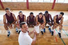 Allenatore sorridente che spiega piano tattico ai giocatori di pallacanestro Fotografie Stock Libere da Diritti