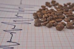 Allenti i chicchi di caffè arrostiti su un tracciato di ECG immagine stock libera da diritti