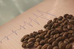 Allenti i chicchi di caffè arrostiti su un tracciato di ECG immagini stock