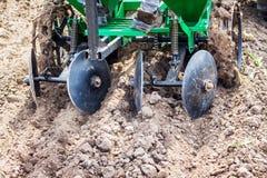 Allenti il suolo facendo uso di un coltivatore Preparazione di suolo nell'ambito della piantatura Lavoro agricolo nello spring_ fotografia stock libera da diritti