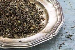 Allenti il tè nero di Darjeeling su un piatto d'argento su dolore blu rustico Fotografie Stock