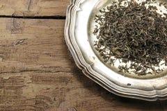 Allenti il tè nero su un piatto d'argento su legno marrone rustico Fotografia Stock