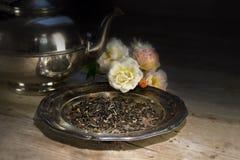 Allenti il tè nero su un vecchio piatto, sulle rose e su una teiera d'argento su Rus Fotografia Stock