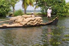 Allepey, †«31-ое марта 2015 Кералы, Индии: Индийский dwell перехода человека с рисом для шлюпок каное подпоров в положении стоковое фото