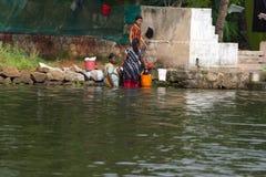 Allepey, Керала, Индия, 31-ое марта 2015: Неопознанное индийское мытье женщины их одежды перед его домом на воде Стоковая Фотография RF