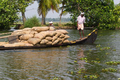 Allepey, Kerala, India – March 31, 2015: Indian man transport dwell with rice for boats. backwaters canoe in state. Allepey, Kerala, India March 31, 2015 Royalty Free Stock Images