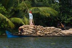 Allepey, Kerala, India †'Marzec 31, 2015: Indiański mężczyzna transport mieszka z ryż dla łodzi stojącej wody czółno w stanie Zdjęcie Stock