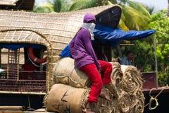 Allepey, Kerala, India, il 31 marzo 2015: Gli uomini non identificati il trasporto, sovraccaricano le borse vuote in barche Fotografia Stock