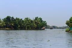 Allepey Kerala, Indien, mars 31, 2015: Den oidentifierade indiska mannen och turister seglar i husbåt på avkrokar Royaltyfria Bilder