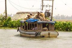Allepey Kerala, Indien, mars 31, 2015: Den oidentifierade indiska mannen och turister seglar i husbåt på avkrokar Royaltyfri Foto