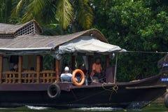 Allepey Kerala, Indien, mars 31, 2015: Den oidentifierade indiska mannen och turister seglar i husbåt på avkrokar Arkivfoto