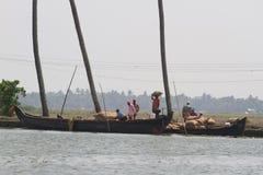 ALLEPPEY, KERALA, INDIA, IL 31 MARZO 2015: Trasporto di alcuni uomini, sovraccarico, messo sopra loro borse cape di riso Immagine Stock