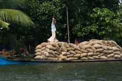 ALLEPPEY, KERALA, INDIA, IL 31 MARZO 2015: Una certa abitazione di trasporto dell'uomo con riso sul canale per le barche Fotografie Stock Libere da Diritti