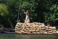 ALLEPPEY, KERALA, INDIA, IL 31 MARZO 2015: Una certa abitazione di trasporto dell'uomo con riso sul canale per le barche Immagini Stock Libere da Diritti