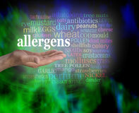 Allergens Word Cloud. Male hand palm facing up with the word ALLERGENS floating above surrounded by a word cloud on a modern green and black vignette background Stock Photo