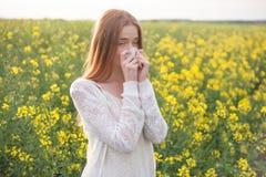 Allergia del polline, ragazza che starnutisce in un campo dei fiori Immagine Stock Libera da Diritti