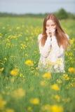 Allergia del polline, ragazza che starnutisce in un campo dei fiori Fotografia Stock