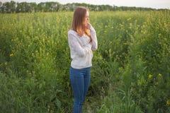 Allergia del polline, ragazza che starnutisce in un giacimento del seme di ravizzone dei fiori Fotografie Stock