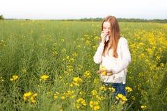 Allergia del polline, ragazza che starnutisce in un giacimento del seme di ravizzone dei fiori Immagine Stock