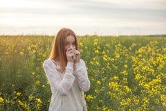 Allergia del polline, ragazza che starnutisce in un giacimento del seme di ravizzone dei fiori Fotografia Stock