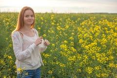 Allergia del polline, ragazza che starnutisce in un giacimento del seme di ravizzone dei fiori Immagini Stock
