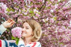 Allergia della primavera Bella donna che gode dell'albero di fioritura della natura Immagine Stock