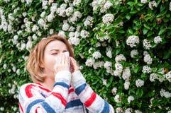Allergia della primavera Donna che soffia vicino all'albero della molla in fioritura Immagine Stock Libera da Diritti