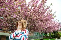 Allergia della primavera Donna che soffia vicino all'albero della molla in fioritura Fotografia Stock