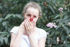allergia La donna ha schiacciato il suo naso con la mano, per non starnutire dal polline dei fiori Donna che protegge il suo naso immagini stock