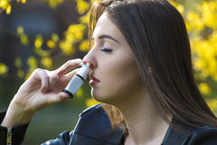 Allergia, ragazza che per mezzo dell'inalatore del naso Fotografia Stock