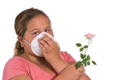 Allergic. A young girl holding a flower while she wears a mask, isolated against a white background Stock Image