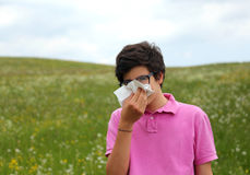 Allergic boy blows his nose with white handkerchief in springtim Royalty Free Stock Image