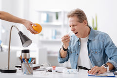 Allergic male going to sneeze. Take vitamins. Frustrated man wearing casual clothes, keeping his mouth wide opened looking at orange Stock Photos