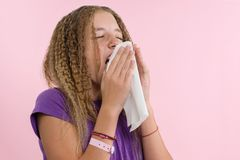 Allergic rhinitis on a summer vacation in a teenage girl`s journey. A girl in a T-shirt on a pink background sneezes into a napki Royalty Free Stock Photo