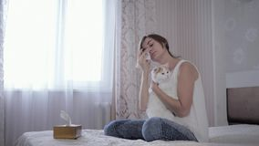 Allergic on fur, young woman spends time with an animal on bed and suffering from respiratory illness sneezes in. Allergic to fur, young woman spends time with stock footage