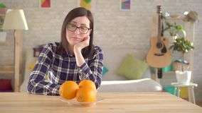 Allergic to oranges.The young woman sniffs and looks at the oranges. Young woman looks at oranges, which cause an allergic reaction.Allergy to orange and citrus stock footage