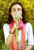 Allergic woman with dandelions in a garden with ye Royalty Free Stock Images