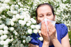 Allergic woman sneezing in handkerchief Royalty Free Stock Photography