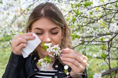 Allergic woman sneezing outdoor on springtime royalty free stock image