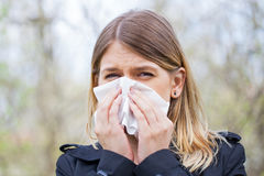 Allergic woman sneezing outdoor on springtime Stock Image