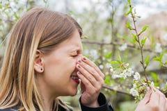 Allergic woman sneezing outdoor on springtime Royalty Free Stock Photos