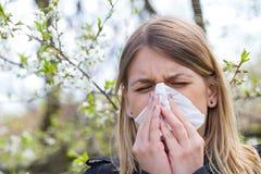 Allergic woman sneezing outdoor on springtime Royalty Free Stock Photo