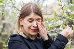 Allergic woman sneezing outdoor on springtime Stock Photography