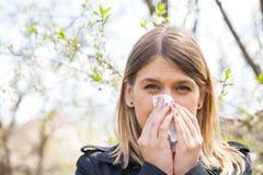 Allergic woman sneezing outdoor on springtime Stock Photos