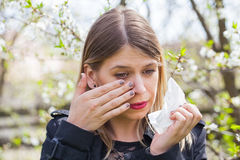 Allergic woman sneezing outdoor on springtime Stock Images