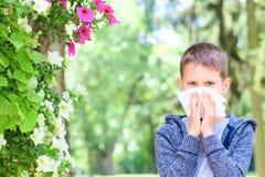 allergie Le petit garçon a des allergies de pollen de fleur images stock