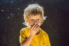 Allergie, zum des Jungenniesens abzuwischen, weil er allergisch ist, Staubfliegen in der Luft abzuwischen, die durch Licht hinter lizenzfreie stockfotografie