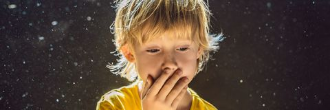 Allergie zum Staub Jungenniesen, weil er allergisch ist, Staubfliegen in der Luft abzuwischen, die durch helle FAHNE hintergrundb stockfotografie