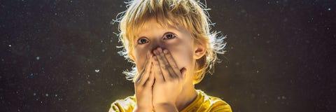 Allergie zum Staub Jungenniesen, weil er allergisch ist, Staubfliegen in der Luft abzuwischen, die durch helle FAHNE hintergrundb stockbild