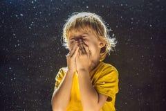 Allergie zum Staub Jungenniesen, weil er allergisch ist, Staubfliegen in der Luft abzuwischen, die durch helle FAHNE hintergrundb lizenzfreie stockbilder